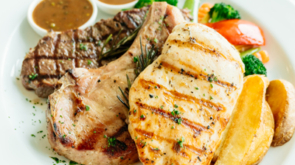 Grilled Chicken breast and Pork chop with beef meat steak and vegetable in white plate